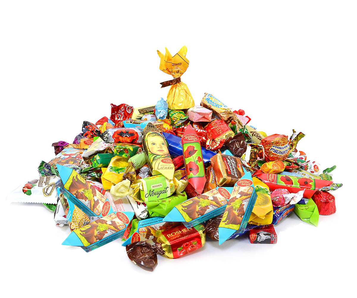 Assorted chocolate and caramel candies in a New Year tin box